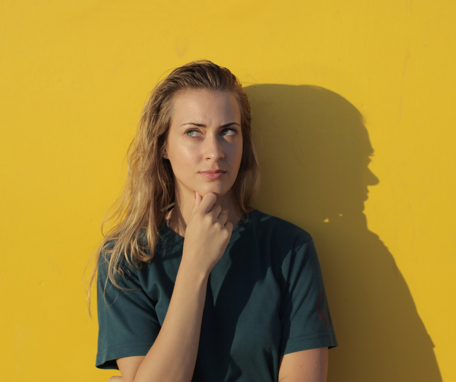 Woman standing in front of a yellow wall with a thoughtful expression on her face