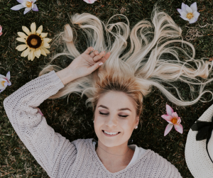 Smiling woman laying on the ground surrounded by flowers