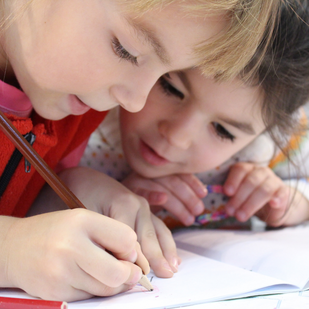 boy and girl working together to draw a picture