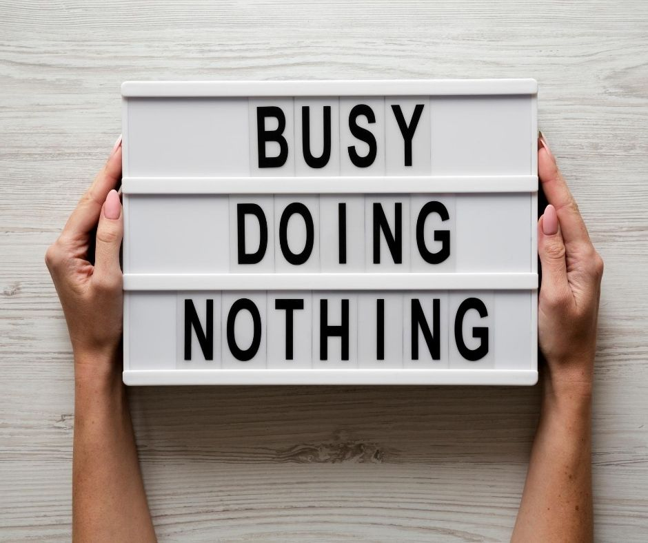 Hands holding a busy doing nothing sign
